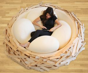 Women laying in a wooden bed shaped like a birds nest