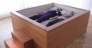 Two people laying in a wooden box shaped bed