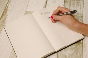 women taking notes inside a notebook