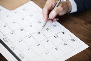 man marking on a calendar
