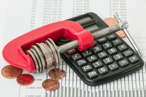 black calculator and cents in side a red clamp