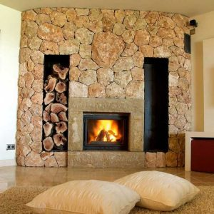large stone wall fire place with wood storage