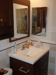 remodeled bathroom sink with wood cabinet