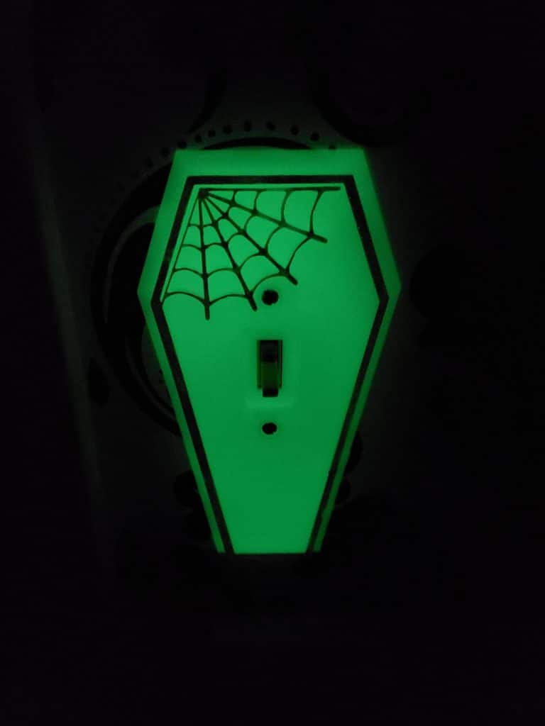 glow in the dark coffin-shaped light switch with spider web