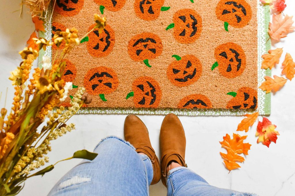 jack o lantern door mat on the ground with fall colored leaves