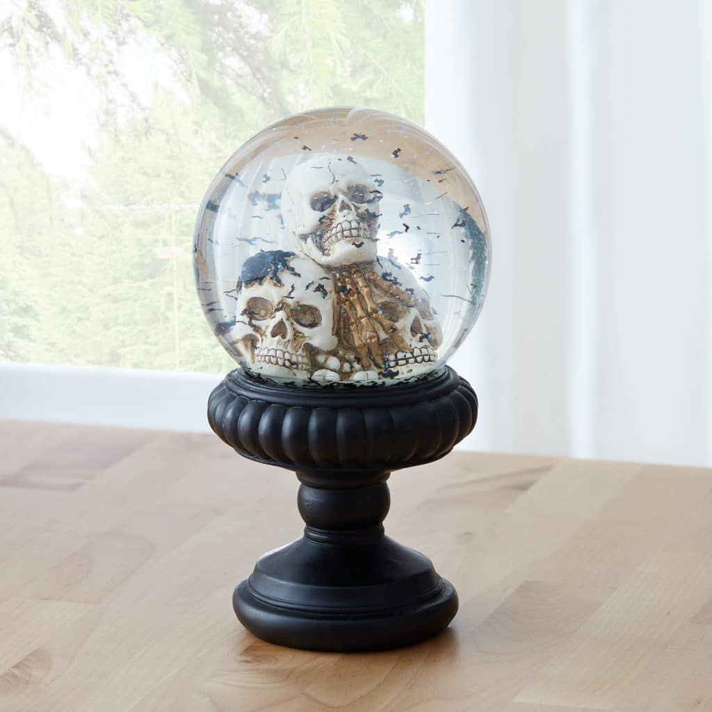 two skulls and small black bats inside a snowglobe with a black holder undeneath on a wooden table next to a window