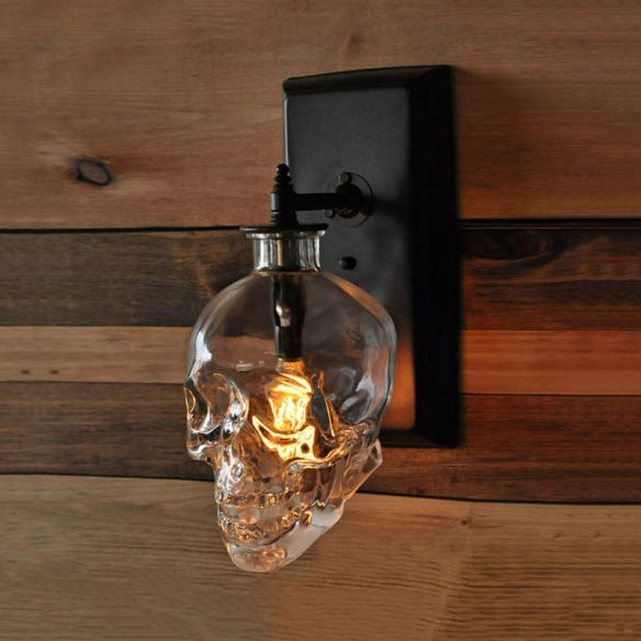 clear skull shaped glass over a lightbulb on the wall
