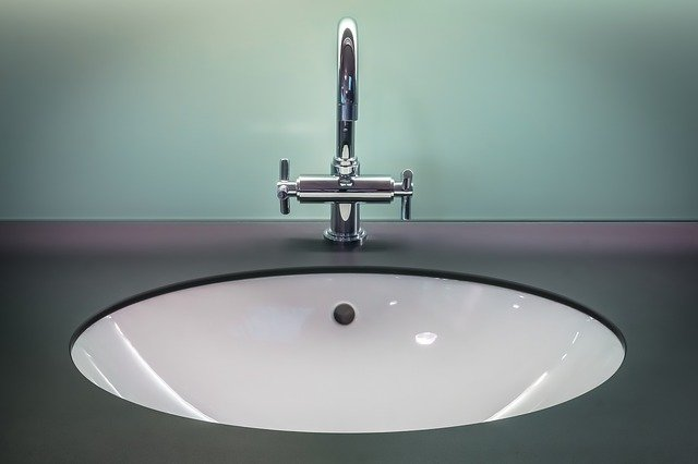 front view of a stainless steel bathroom sink with a black countertop
