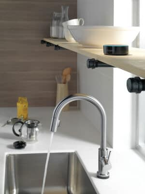 stainless steel kitchen sink faucet with water shooting out into sink