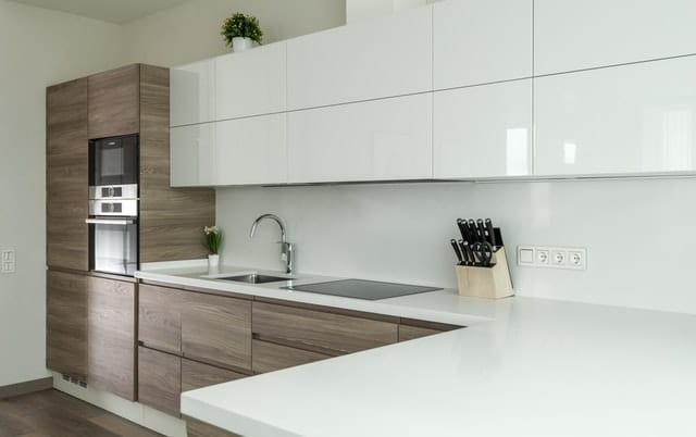 modern updated kitchen with white simple cabinets and wood features