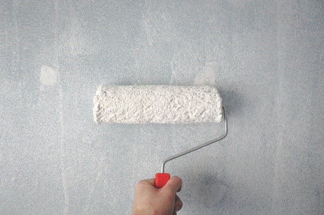 paint roller with white paint on a kitchen wall